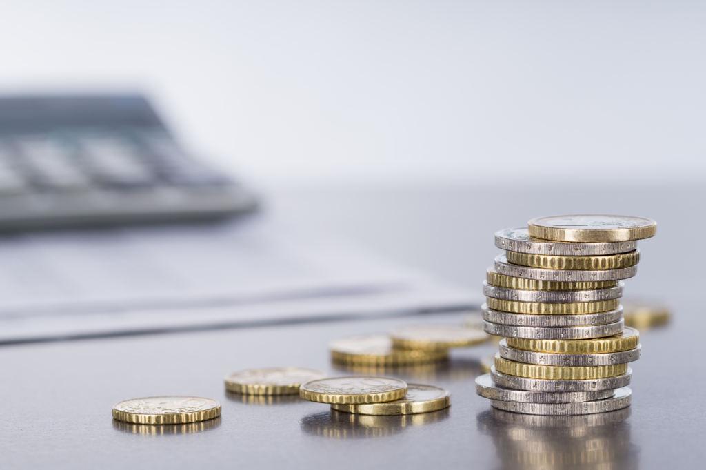 Euromünzen und Taschenrechner auf spiegelnder Tischplatte beim Haus verkaufen in Vorarlberg in Bregenz und Lustenau